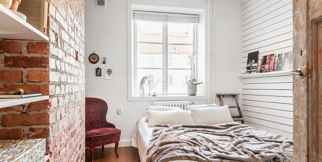 Mała sypialnia z ceglaną ścianą