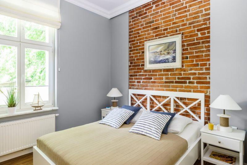 Marynistyczne wnętrze podkreślone ceglaną ścianą
