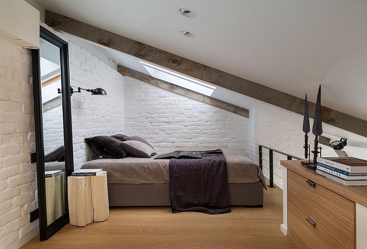 Męski charakter mieszkania podkreślony białą, ceglaną ścianą