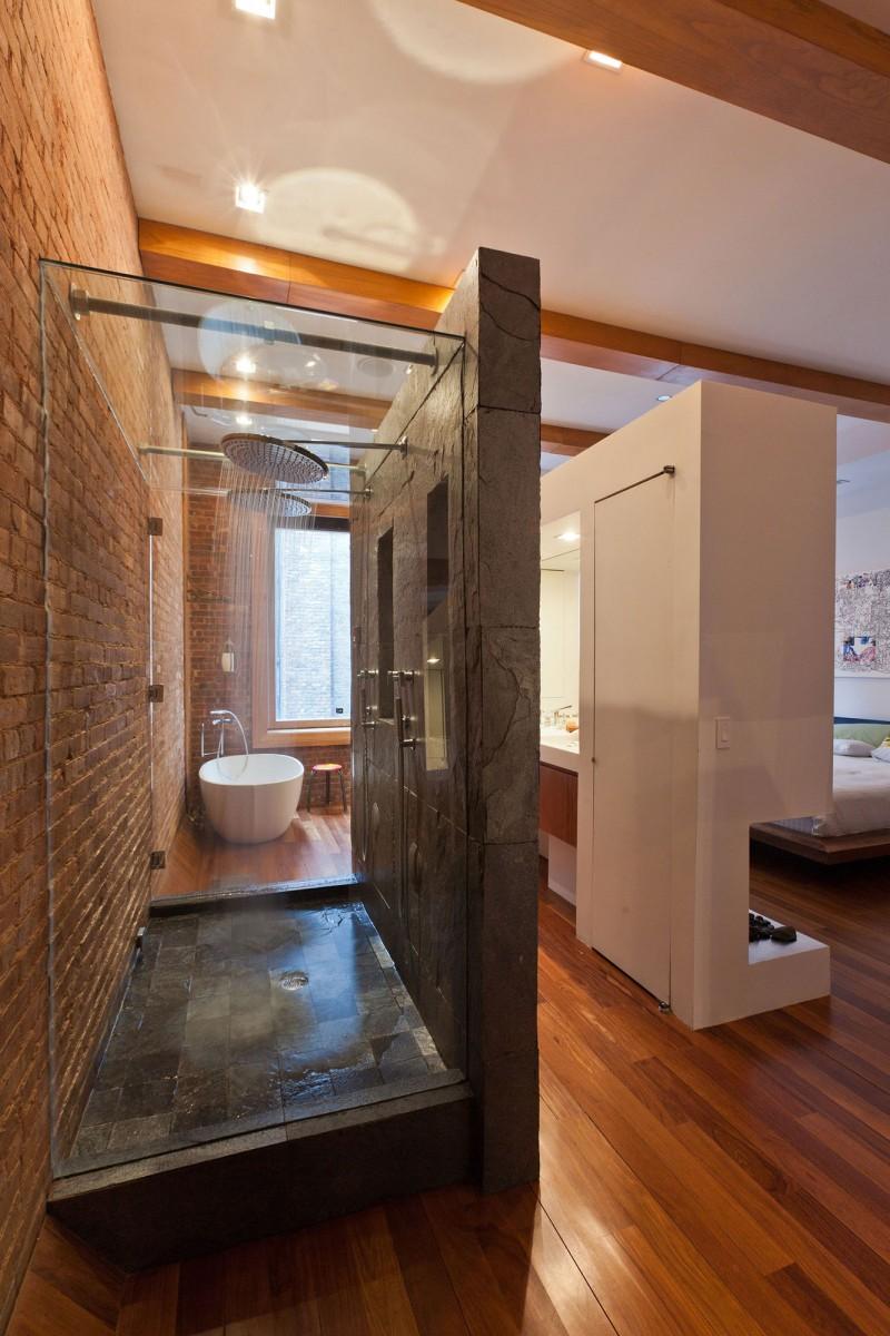 Ceglane ściany, kamień, szkło i drewno w łazience